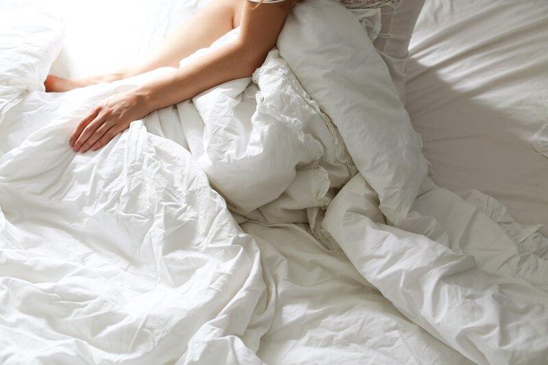 človek ležiaci v bielej posteli