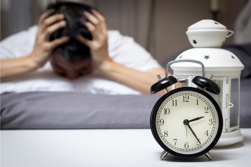 muž trpiaci insomniou a hodiny